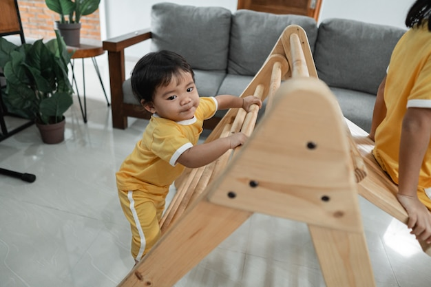Little kids climb on the pikler triangle toy while playing together in the living room