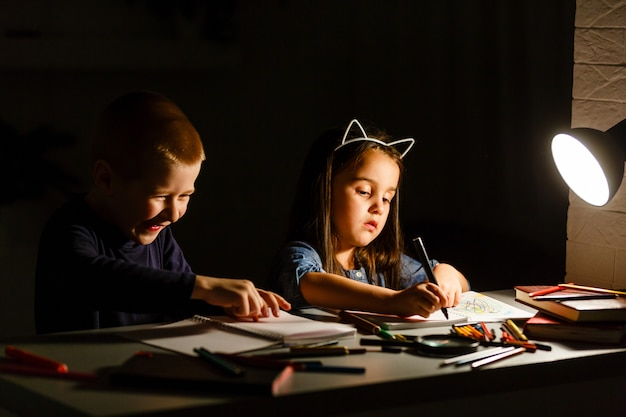 Little kids doing homework in evening at home