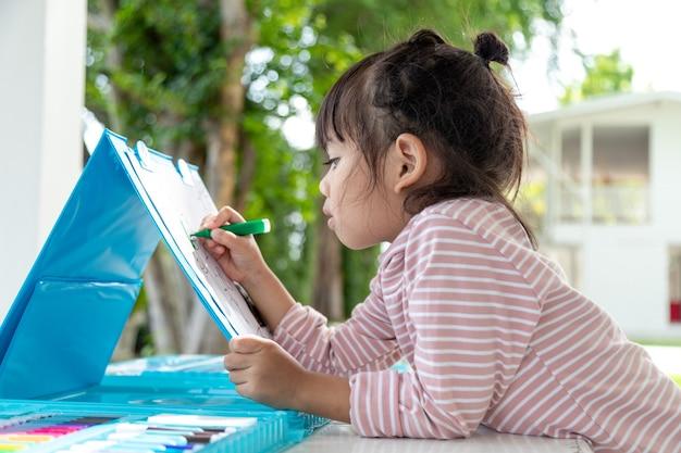 색연필로 그림을 그리는 어린 아이들은 아이들의 창의력과 손글씨 실력을 향상시키는 좋은 활동입니다. 교육 및 학습 취미에 대한 개념 그림입니다.
