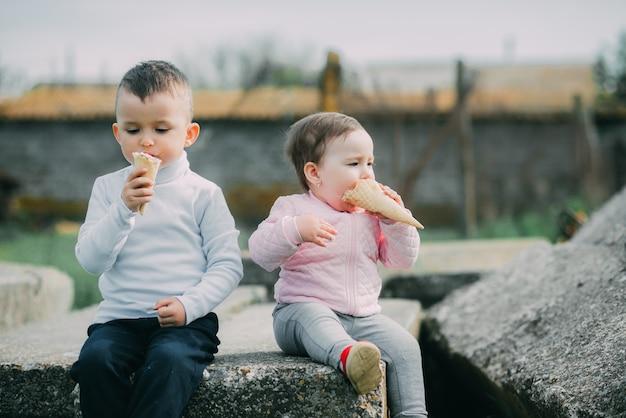 村の屋外でアイスクリームを食べる小さな子供たち