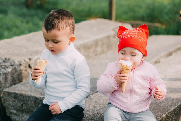 Little kids eating ice cream outdoors in the village