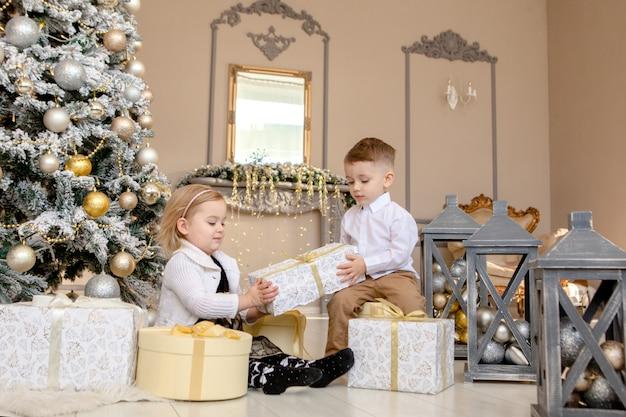 Маленькие дети дружба и любовь. маленький мальчик дает маленькой девочке подарок на рождество