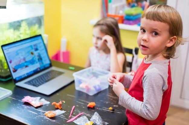 어린 아이들, 소녀, 소년, 테이블에 있는 방에서 점토나 플라스틱으로 창의적인 모델링에 참여하고 컴퓨터나 노트북에서 온라인 수업을 시청합니다. 원격 가정 학습. 모델링 반죽