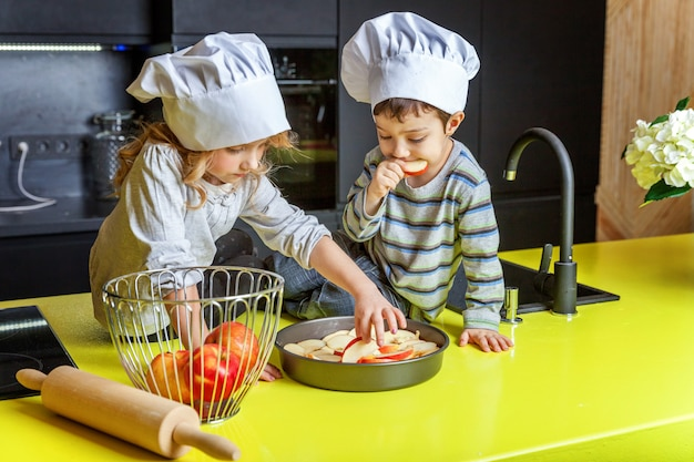 Little kids girl and boy with chef hat preparing bake homemade apple pie in kitchen