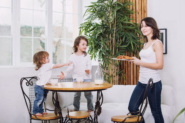 Little kids girls are beautiful and cute with their mother at home together eating cookies