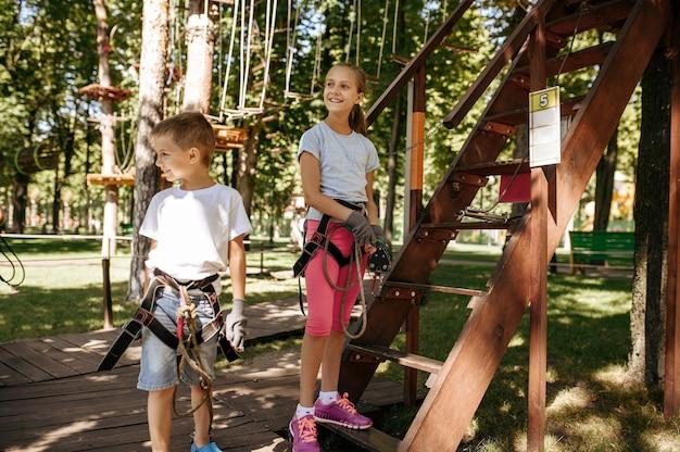 機器、ロープパーク、遊び場の小さな子供たち。吊橋に登る子供たち
