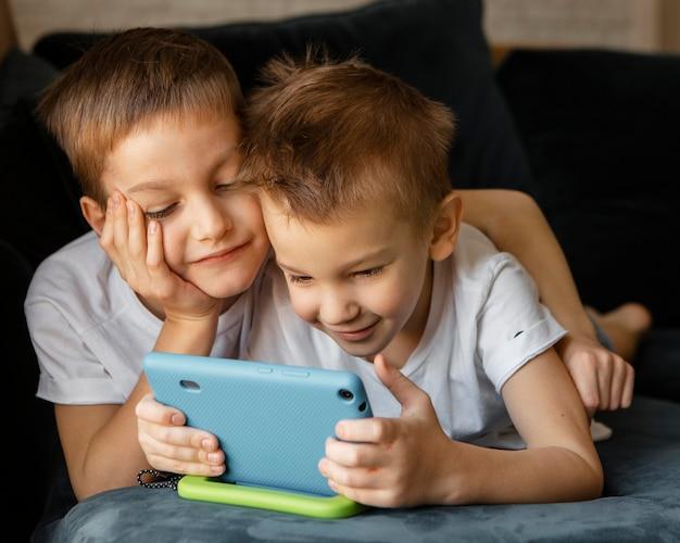Маленькие дети вместе смотрят по телефону дома