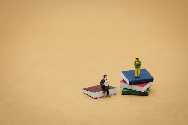 Little kids miniature people standing on books using as background education