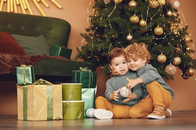 Маленькие дети возле елки в сером свитере