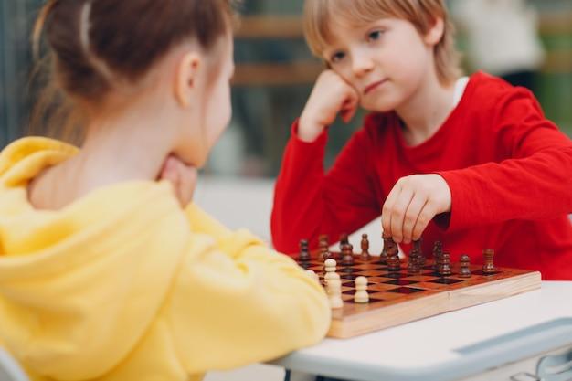 Маленькие дети играют в шахматы в детском саду или начальной школе.