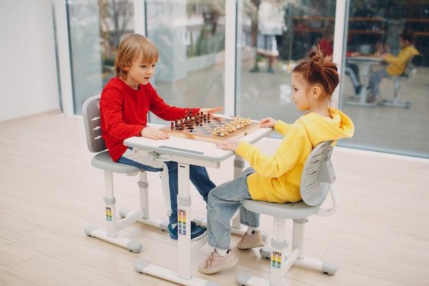 Маленькие дети играют в шахматы в детском саду или начальной школе