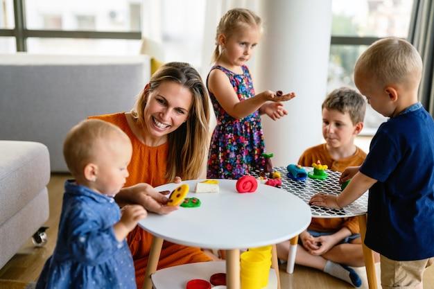 粘土で遊んでいる小さな子供たち。先生やお母さんは子供と遊ぶ。人々、子供の創造性の概念