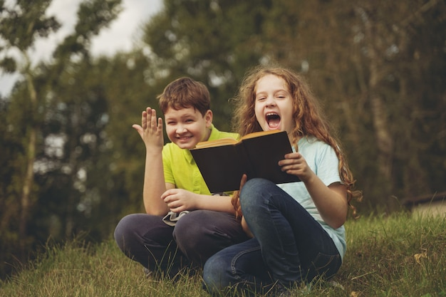 Little kids reading the book outdoors. education concept.