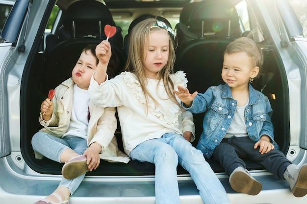 도로 여행 전에 차 트렁크에 앉아있는 어린 아이들