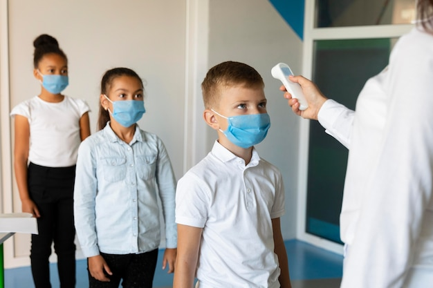 先生が体温を測るのを待っている小さな子供たち
