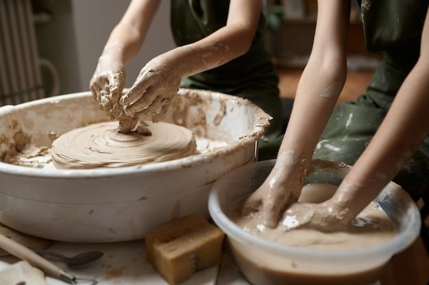 Маленькие дети работают на гончарном круге в мастерской, вид сбоку на руках. урок лепки из глины в художественной школе. юные мастера народных промыслов, приятное увлечение, счастливое детство.
