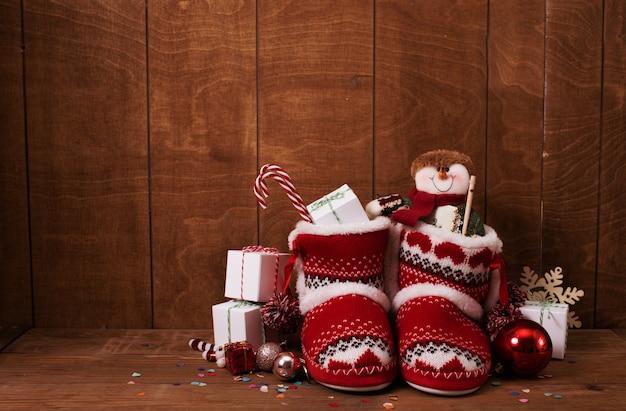 クリスマスプレゼントやさまざまな装飾が施された小さなニットブーツ。
