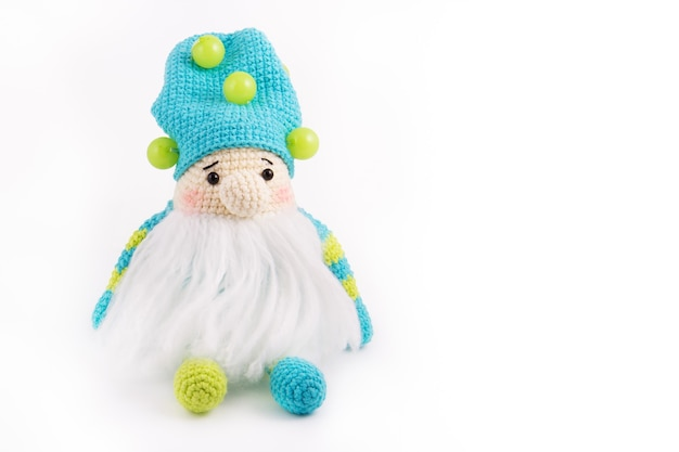 Little knitted gnome on a white