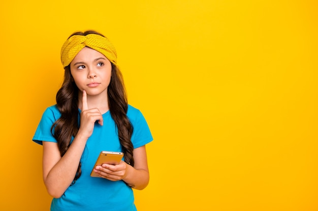 小さな女性はあごに電話の指を持って空きスペースを見てください