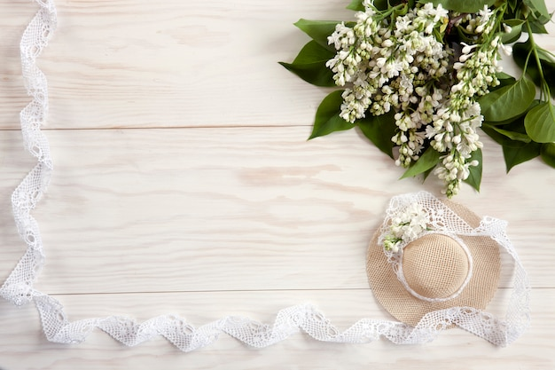 Little  lady's hat with lace on white wooden background with lilac branches.