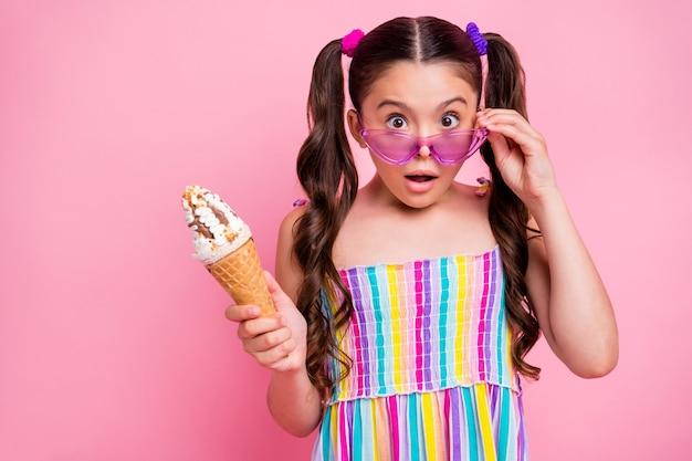 Маленькая леди снимает солнцезащитные очки с открытым ртом и держит мороженое
