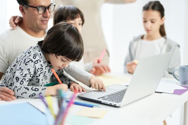 집에서 가족과 시간을 보내며 그림을 그리는 동안 집중하는 모습을 보이는 작은 라틴 소년. 아버지는 집에서 일하고 아이들을 보면서 노트북을 사용합니다. 프리랜서, 가족 개념