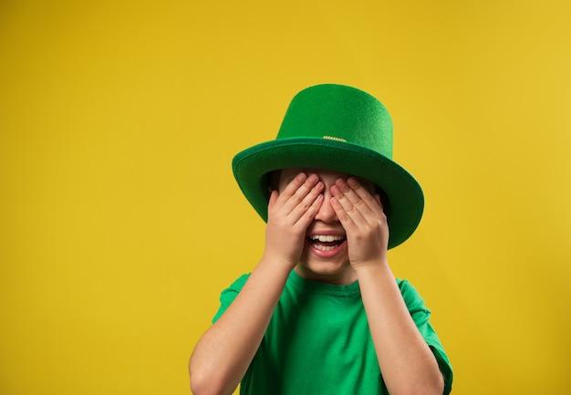 緑のアイルランドのレプラコーンの帽子をかぶった小さな笑いの少年は彼の手のひらで彼の目を覆います