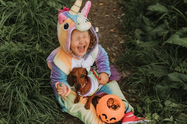Little laughing girl and a dog in halloween costumes with a pumpkin basket for sweets outdoors