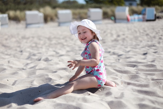 Little laughing girl on white sand beach enjoying summer and vacation
