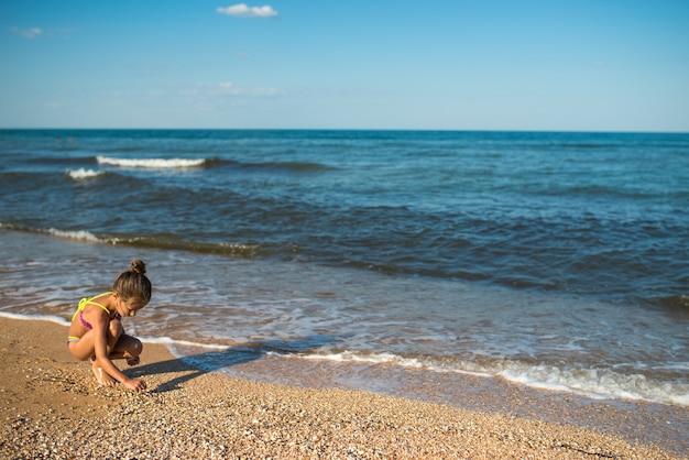 외로운 소녀는 바다를 배경으로 앉아있는 동안 모래 위에 무언가를 씁니다.