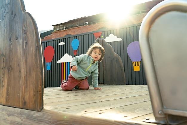 야외 나무 놀이터에서 무릎을 꿇고 기어가는 장발 소년