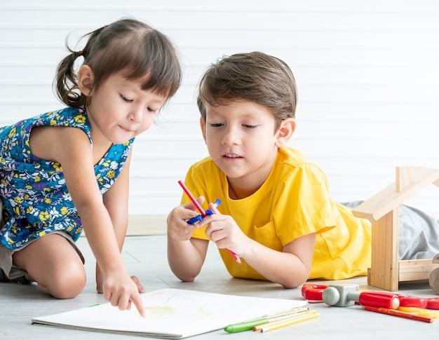 少し素敵な男の子と女の子が床でおもちゃを遊んでいる、子供のための教育ゲーム。兄と妹のコンセプト。