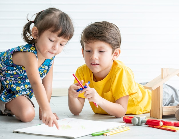 Little lovely boy and girl playing toys on the floor,educational games for kids.brother and sister concept.