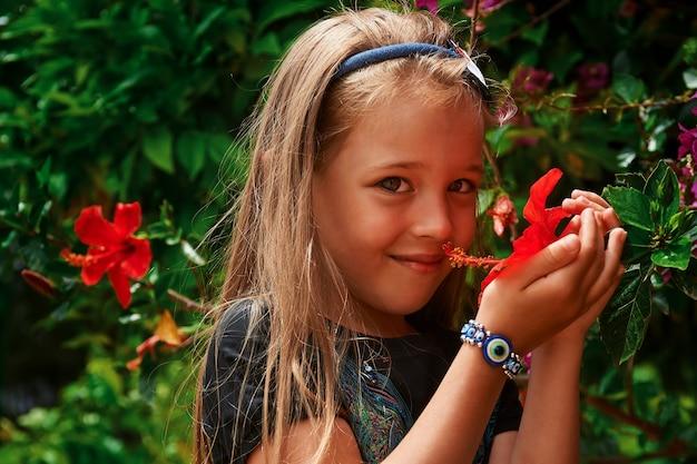 美しい庭で花を持つ小さな素敵な女の子