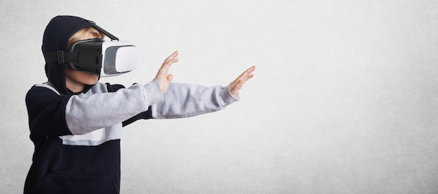 スウェットシャツと仮想現実の眼鏡の小さな男性の子供が手でジェスチャーし、それらを前方に伸ばし、仮想環境と相互作用します
