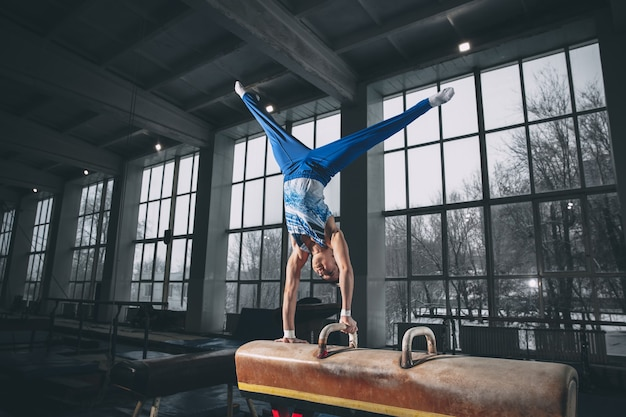 Little male gymnast training in gym, composed and active.