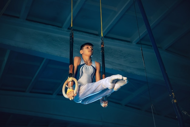 Little male gymnast training in gym, flexible and active. caucasian fit boy, athlete in white sportswear practicing in exercises for balance on the rings. movement, action, motion, dynamic concept.