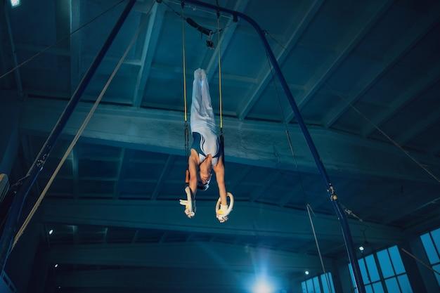 Piccola ginnasta maschio che si allena in palestra, flessibile e attiva. ragazzo in forma caucasica, atleta in abiti sportivi bianchi che praticano esercizi per l'equilibrio sugli anelli.