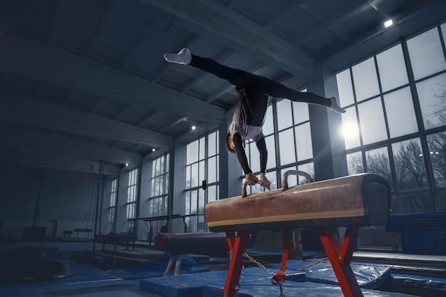 Little male gymnast training in gym, flexible and active. caucasian fit little boy, athlete in sportswear practicing in exercises for strength, balance. movement, action, motion, dynamic concept.