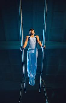 Piccola ginnasta maschio che si allena in palestra, flessibile e attiva