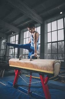 체육관에서 작은 남자 체조 훈련, 구성 및 활동. 백인 맞는 어린 소년, 운동복에 운동 선수가 힘, 균형을 위해 연습합니다. 동작, 동작, 동작, 동적 개념