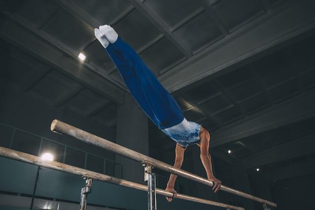 体育館で小さな男性の体操選手が、落ち着いて活動的にトレーニングしている。コーカサス地方の少年、スポーツウェアを着たアスリートが、強さ、バランスの練習をしている。動き、アクション、動き、ダイナミックなコンセプト