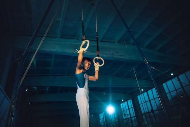 ジムでの小さな男性体操選手のトレーニング、柔軟でアクティブ。白人のフィットの少年、白いスポーツウェアを着たアスリートが、リングのバランスの練習をしている。動き、アクション、動き、ダイナミックなコンセプト。