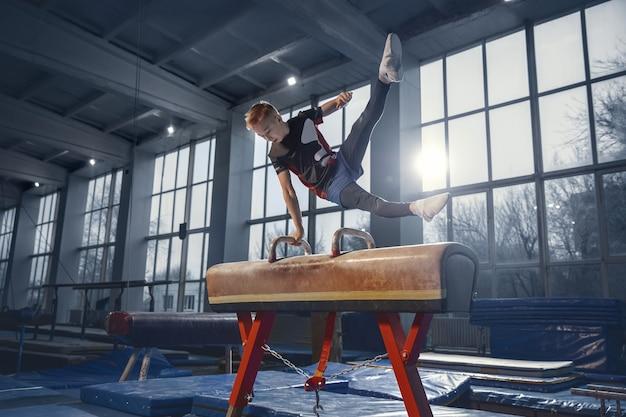 ジムでの小さな男性体操選手のトレーニング、柔軟でアクティブ。コーカサス地方の少年、スポーツウェアを着たアスリートが、強さ、バランスの練習をしている。動き、アクション、動き、ダイナミックなコンセプト。