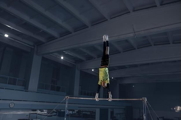 유연하고 활동적인 체육관에서 작은 남자 체조 훈련. 백인 맞는 어린 소년, 운동복에 운동 선수가 힘, 균형을 위해 연습합니다. 움직임, 행동, 움직임, 역동적 인 개념. 프리미엄 사진