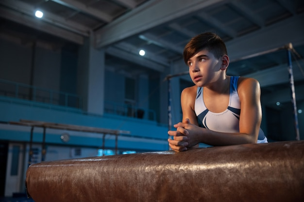 유연하고 활동적인 체육관에서 작은 남자 체조 훈련. 백인 맞는 어린 소년, 자신감을 게시하는 흰색 운동복 선수.