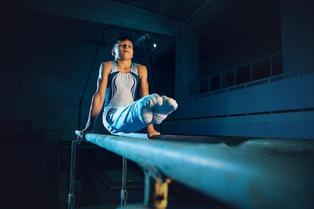 ジムでの小さな男性体操選手のトレーニング、柔軟でアクティブ。白人の小さな男の子、体力、バランスのためのエクササイズで練習している白いスポーツウェアのアスリート。動き、アクション、動き、ダイナミックなコンセプト。