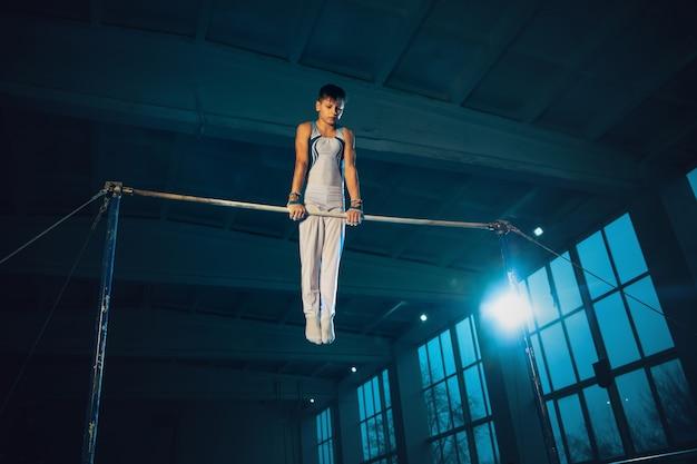 Маленький гимнастка тренируется в тренажерном зале, гибкий и активный. кавказский маленький мальчик, спортсмен в белой спортивной одежде, упражнения на силу, баланс. движение, действие, движение, динамическая концепция.