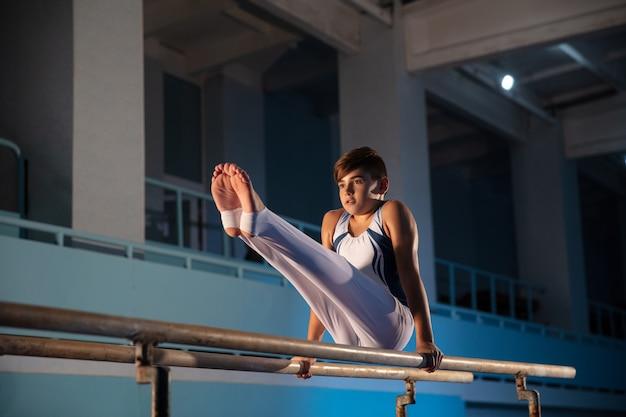 Маленький мужской гимнаст тренируется в тренажерном зале, гибкий и активный