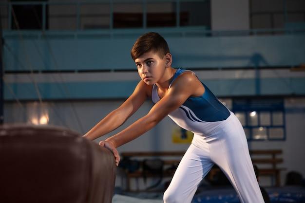 ジムでの小さな男性体操選手のトレーニング